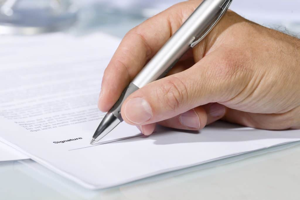 Close up of person signing a document