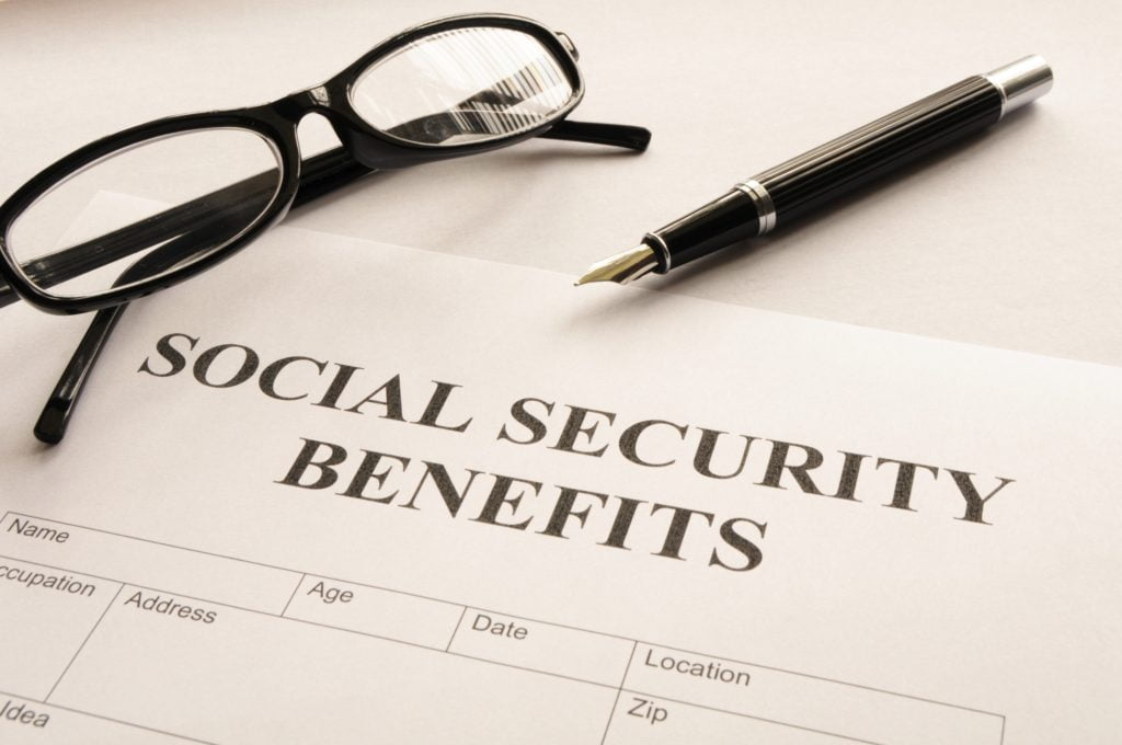 Social Security Benefits form with a pen and glasses