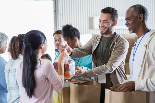 Volunteers hand out bags of food during food drive