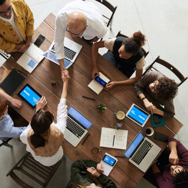 Multiple team members meeting with laptops and tablets